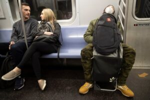 photo of 3 people on a subway car. One is wearing a face mask. Two do not. What should you do if you are returning to public transport? AP Photo by Mary Altaffer, Time, 3/11/2-2020